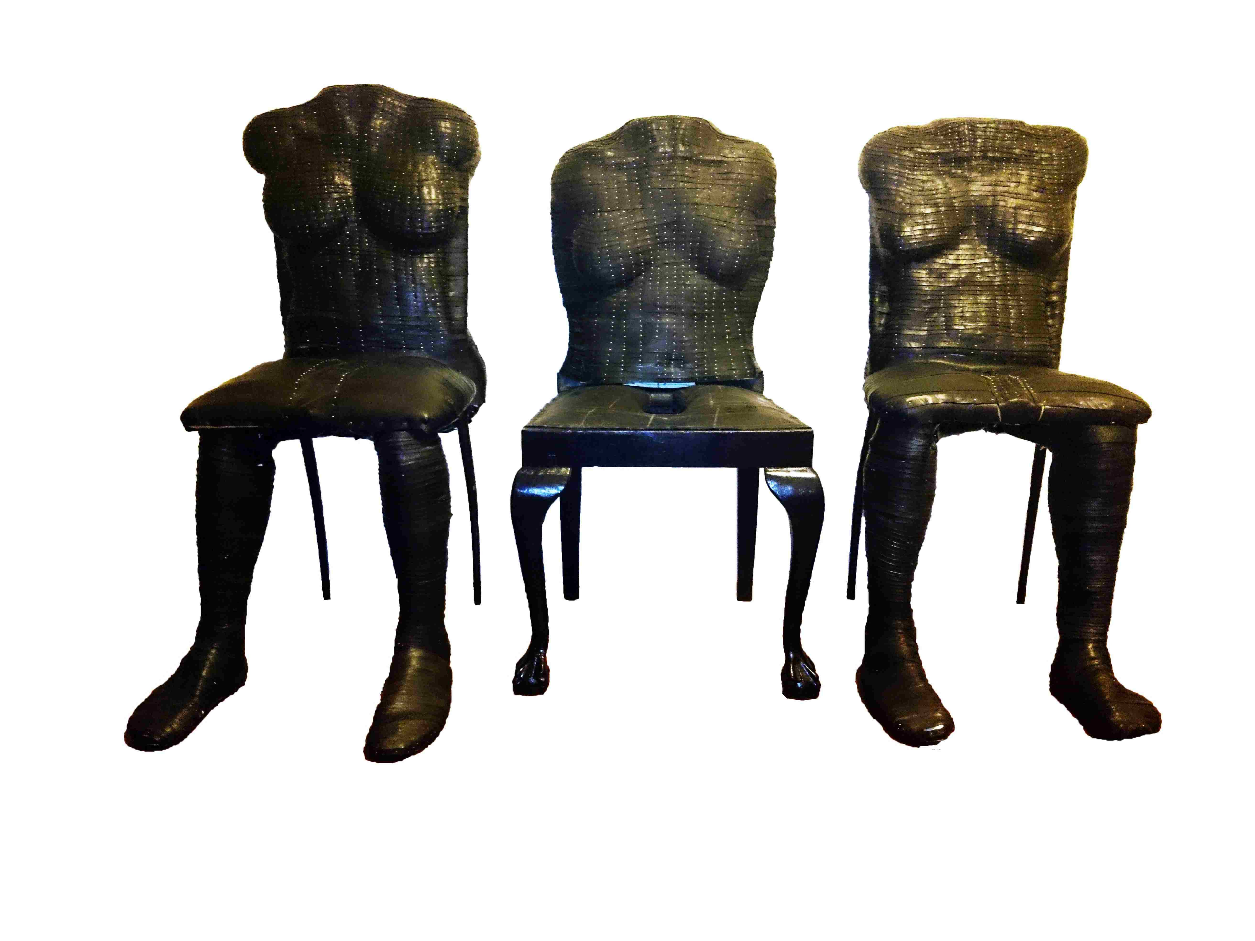 A trio of figurative sculptures of headless, armless, female torsos on the backs of chairs covered in strips of rubber and thousands of silver sewing pins.