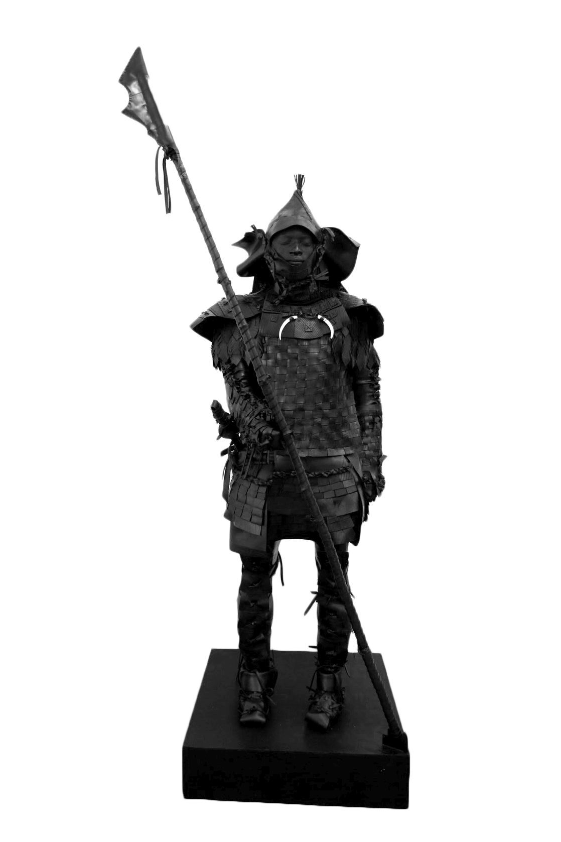 An interpretation of Yasuke, a samurai of black African descent, wearing a woven breastplate decorated with two animal fangs and holding a long spear.